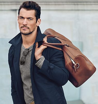 A man carrying a tan leather holdall
