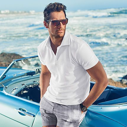 David Gandy wearing white polo shirt and checked swim shorts
