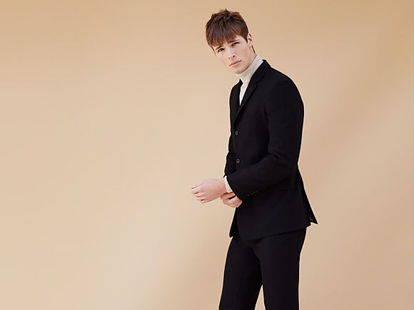 Manwearing black suit and roll neck jumper