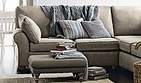 A corner sofa, cushions and throws