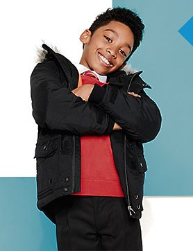 A boy wearing a black coat and red school jumper