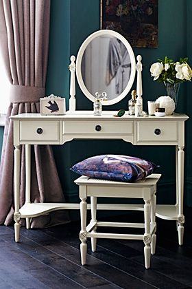 A white dressing table with mirror and matching seat