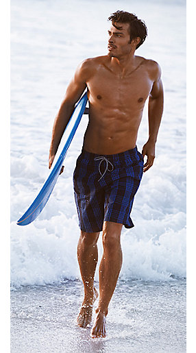 Man wearing blue swim shorts with a surfboard on a beach