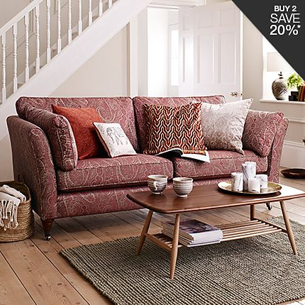 A patterned sofa with cushions and a coffee table