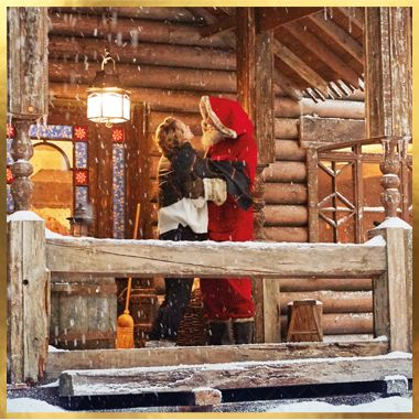 Mrs Claus with her husband at their log cabin
