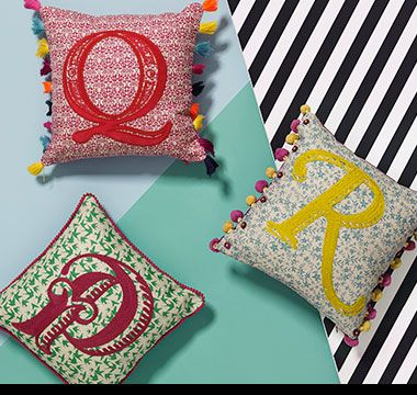 Three embroidered alphabet cushions
